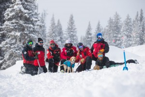 Ski patrollers at avalanche dog course with dog