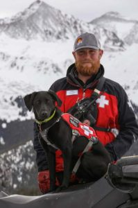 Dog handler with black lab on snowmobile